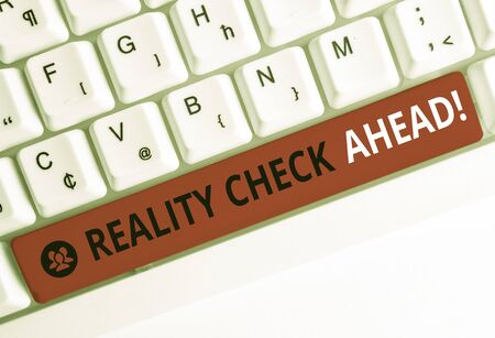 Writing note showing Reality Check Ahead. Business concept for makes them recognize truth about situations or difficulties White pc keyboard with note paper above the white background
