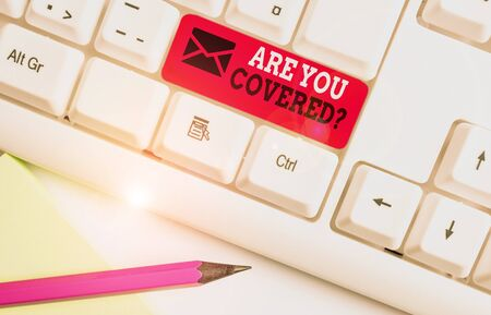 Handwriting text Are You Covered Question. Conceptual photo asking showing if they had insurance in work or life White pc keyboard with empty note paper above white background key copy space Zdjęcie Seryjne