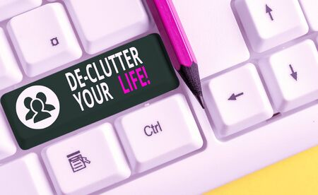 Conceptual hand writing showing De Clutter Your Life. Concept meaning remove unnecessary items from untidy or overcrowded places White pc keyboard with note paper above the white background