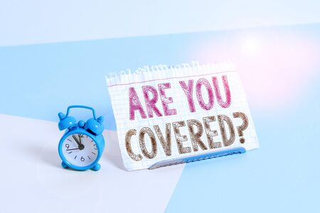 Word writing text Are You Covered Question. Business photo showcasing asking showing if they had insurance in work or life Mini size alarm clock beside a Paper sheet placed tilted on pastel backdrop