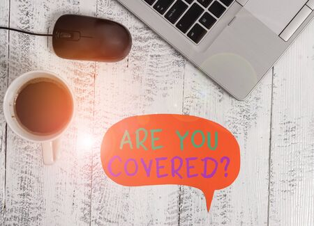 Handwriting text Are You Covered Question. Conceptual photo asking showing if they had insurance in work or life Open metallic laptop speech bubble mouse coffee cup vintage wooden table Zdjęcie Seryjne