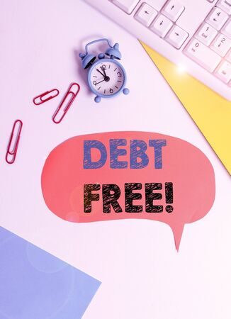 Text sign showing Debt Free. Business photo text does not owning any money to any individual or companies Flat lay above table with copy space on the bubble paper with clock and paper clips