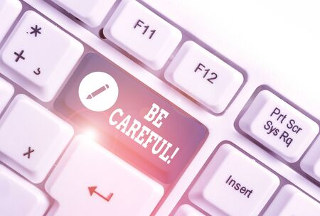 Conceptual hand writing showing Be Careful. Concept meaning making sure of avoiding potential danger mishap or harm White pc keyboard with note paper above the white background