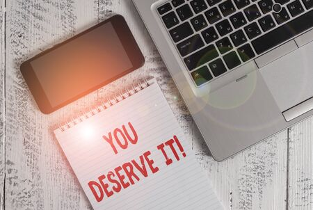 Text sign showing You Deserve It. Business photo showcasing should have it because of their qualities or actions Metallic laptop blank ruled notepad smartphone lying old wooden table