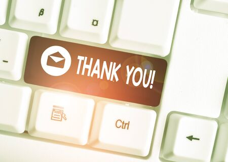 Text sign showing Thank You. Business photo showcasing polite expression used when acknowledging gift service compliment White pc keyboard with empty note paper above white background key copy space 스톡 콘텐츠