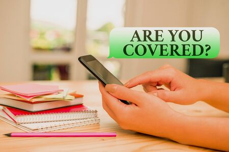 Writing note showing Are You Covered Question. Business concept for asking showing if they had insurance in work or life woman using smartphone and technological devices inside the home Zdjęcie Seryjne