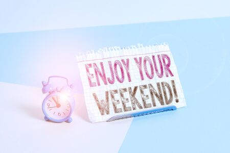 Word writing text Enjoy Your Weekend. Business photo showcasing wishing someone that something nice will happen at holiday Mini size alarm clock beside a Paper sheet placed tilted on pastel backdrop Stock fotó