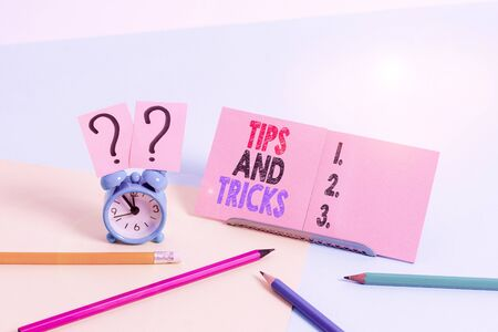 Conceptual hand writing showing Tips And Tricks. Concept meaning means piece advice maybe suggestion how improve Mini size alarm clock beside stationary on pastel backdrop