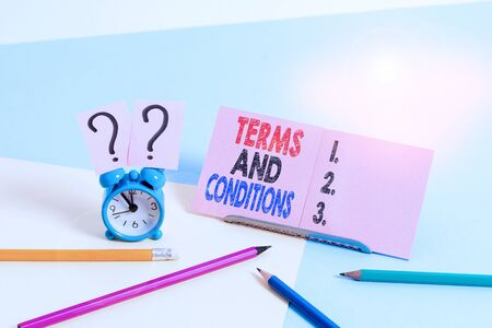 Conceptual hand writing showing Terms And Conditions. Concept meaning rules that apply to fulfilling a particular contract Mini size alarm clock beside stationary on pastel backdrop Reklamní fotografie