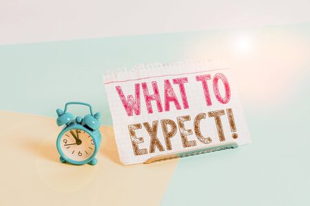 Word writing text What To Expect. Business photo showcasing asking about regard something as likely to happen occur Mini size alarm clock beside a Paper sheet placed tilted on pastel backdrop