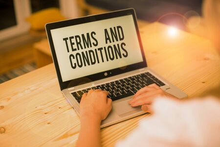 Writing note showing Terms And Conditions. Business concept for rules that apply to fulfilling a particular contract woman with laptop smartphone and office supplies technology Reklamní fotografie