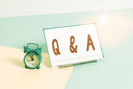 Word writing text Q And A. Business photo showcasing defined as questions being asked and answers Mini size alarm clock beside a Paper sheet placed tilted on pastel backdrop Banco de Imagens