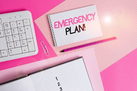 Writing note showing Emergency Plan. Business concept for actions developed to mitigate damage of potential events Writing equipments and computer stuffs placed above colored plain table