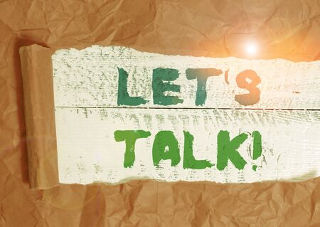 Conceptual hand writing showing Let S Is Talk. Concept meaning suggesting in the beginning of a conversation on the topic Cardboard which is torn placed above a wooden classic table