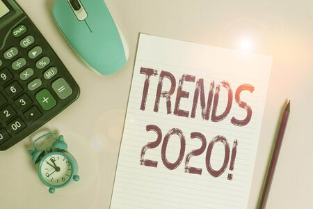 Conceptual hand writing showing Trends 2020. Concept meaning general direction in which something is developing or changing Electronic calculator alarm clock sheet pencil colored background