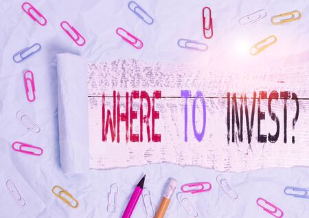 Word writing text Where To Invest Question. Business photo showcasing asking about where put money into financial schemes or shares Stationary and torn cardboard placed above a wooden classic table backdrop