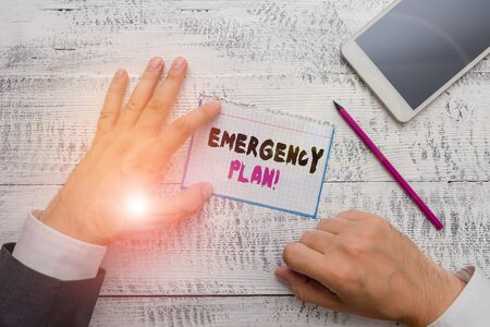 Conceptual hand writing showing Emergency Plan. Concept meaning actions developed to mitigate damage of potential events Hand hold note paper near writing equipment and smartphone 版權商用圖片