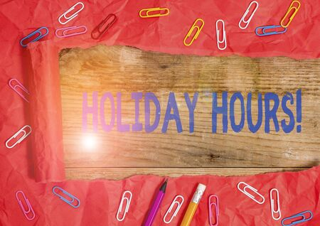 Handwriting text writing Holiday Hours. Conceptual photo Overtime work on for employees under flexible work schedules Stationary and torn cardboard placed above a wooden classic table backdrop