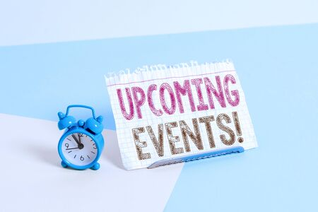 Word writing text Upcoming Events. Business photo showcasing thing that will happens or takes place soon planned occasion Mini size alarm clock beside a Paper sheet placed tilted on pastel backdrop Stock fotó