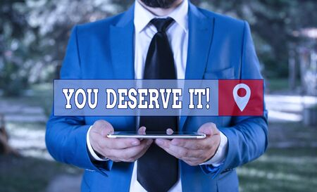 Writing note showing You Deserve It. Business concept for should have it because of their qualities or actions Businessman in blue suite with a tie holds lap top in hands