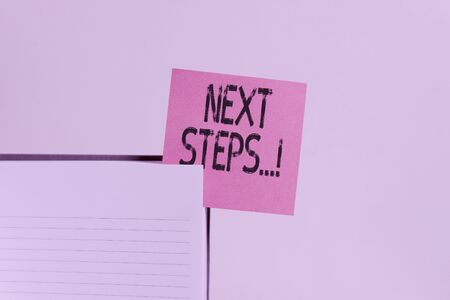 Text sign showing Next Steps. Business photo showcasing something you do after you have finished doing first one Upper view lined hard cover note book sticky note inserted clear background