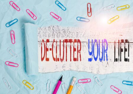 Word writing text De Clutter Your Life. Business photo showcasing remove unnecessary items from untidy or overcrowded places Stationary and torn cardboard placed above a wooden classic table backdrop