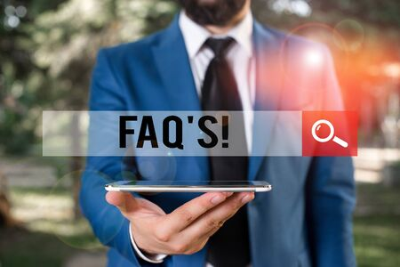 Handwriting text writing Faq S. Conceptual photo list of questions and answers relating to particular subject Businessman in blue suite with a tie holds lap top in hands