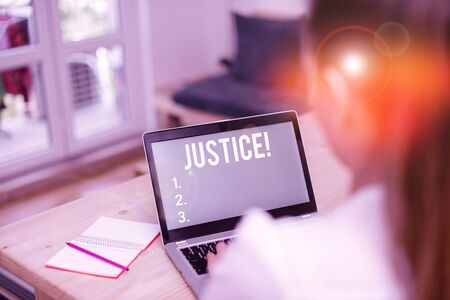 Word writing text Justice. Business photo showcasing impartial adjustment of conflicting claims or assignments woman laptop computer office supplies technological devices inside home
