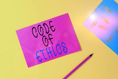 Writing note showing Code Of Ethics. Business concept for basic guide for professional conduct and imposes duties Blank paper sheets message pencil clips binder plain colored background