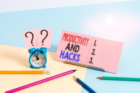 Conceptual hand writing showing Productivity Hacks. Concept meaning tricks that you get more done in the same amount of time Mini size alarm clock beside stationary on pastel backdrop
