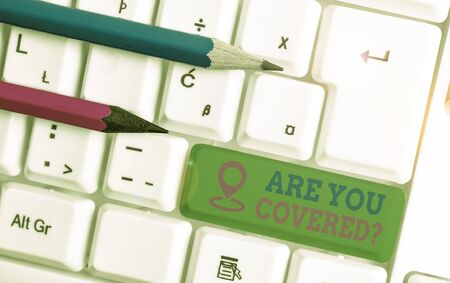 Text sign showing Are You Covered Question. Business photo text asking showing if they had insurance in work or life White pc keyboard with empty note paper above white background key copy space
