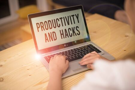 Writing note showing Productivity Hacks. Business concept for tricks that you get more done in the same amount of time woman with laptop smartphone and office supplies technology