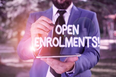 Conceptual hand writing showing Open Enrolments. Concept meaning when employees may make changes to elected fringe benefit Businessman in blue suite stands with mobile phone in hands