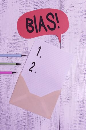 Conceptual hand writing showing Bias. Concept meaning inclination or prejudice for or against one demonstrating group Envelope speech bubble ballpoints lying wooden retro background Banco de Imagens