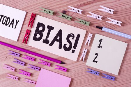 Handwriting text writing Bias. Conceptual photo inclination or prejudice for or against one demonstrating group Colored clothespin papers empty reminder wooden floor background office