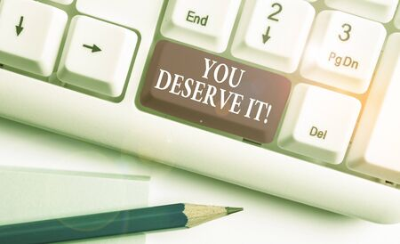 Text sign showing You Deserve It. Business photo text should have it because of their qualities or actions White pc keyboard with empty note paper above white background key copy space