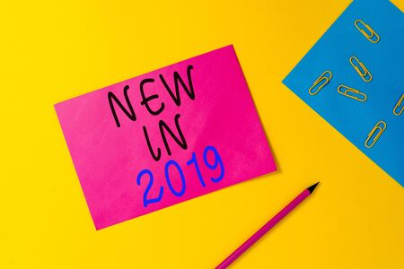 Writing note showing New In 2019. Business concept for what will be expecting or new creation for the year 2019 Blank paper sheets message pencil clips binder plain colored background Stock Photo