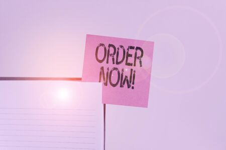 Text sign showing Order Now. Business photo showcasing confirmed request by one party to another to buy sell Upper view lined hard cover note book sticky note inserted clear background Banque d'images