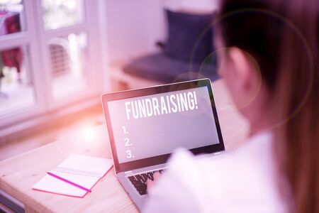 Word writing text Fundraising. Business photo showcasing seeking to generate financial support for charity or cause woman laptop computer office supplies technological devices inside home Stock Photo