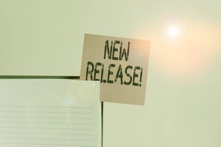 Text sign showing New Release. Business photo showcasing announcing something newsworthy recent product Upper view lined hard cover note book sticky note inserted clear background