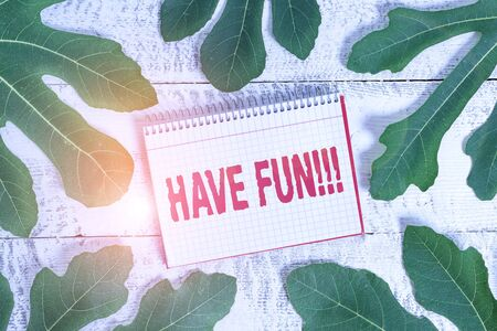 Conceptual hand writing showing Have Fun. Concept meaning wish somebody good and enjoyable time when they do something Leaves surrounding notepaper above a classic wooden table