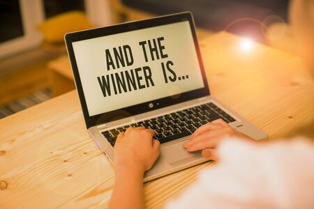 Writing note showing And The Winner Is. Business concept for announcing a demonstrating or thing that wins something woman with laptop smartphone and office supplies technology