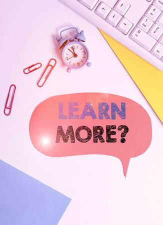 Text sign showing Learn More question. Business photo text gain knowledge or skill studying practicing Flat lay above table with copy space on the bubble paper with clock and paper clips