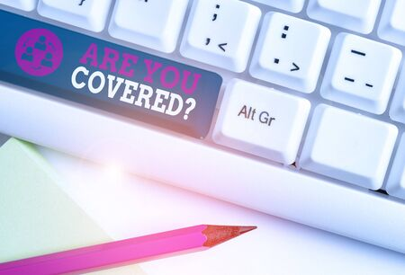Conceptual hand writing showing Are You Covered Question. Concept meaning asking showing if they had insurance in work or life White pc keyboard with note paper above the white background