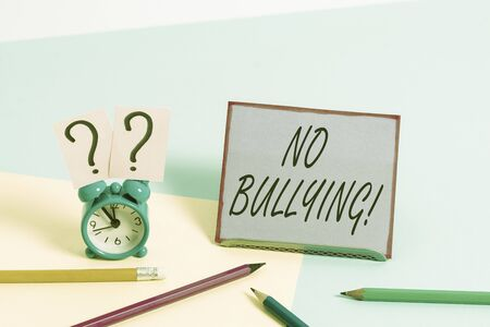 Conceptual hand writing showing No Bullying. Concept meaning stop aggressive behavior among children power imbalance Mini size alarm clock beside stationary on pastel backdrop