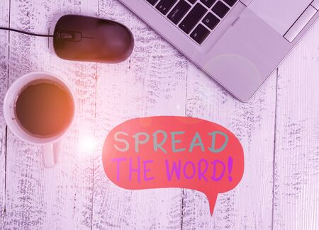 Handwriting text Spread The Word. Conceptual photo share the information or news using social media Open metallic laptop speech bubble mouse coffee cup vintage wooden table