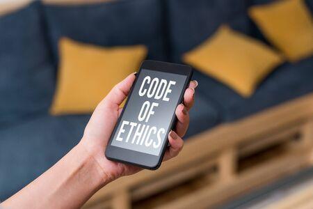 Writing note showing Code Of Ethics. Business concept for basic guide for professional conduct and imposes duties woman using smartphone and technological devices inside the home