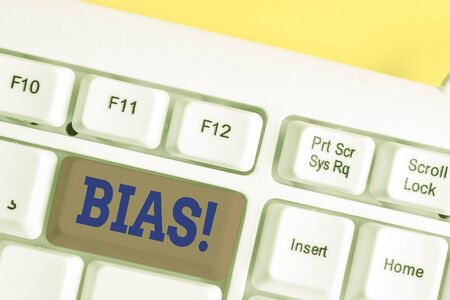 Writing note showing Bias. Business concept for inclination or prejudice for or against one demonstrating group White pc keyboard with note paper above the white background Banco de Imagens