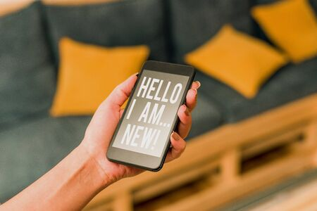 Writing note showing Hello I Am New. Business concept for used as greeting or to begin telephone conversation woman using smartphone and technological devices inside the home