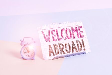 Word writing text Welcome Abroad. Business photo showcasing something that you say when someone gets on ship Mini size alarm clock beside a Paper sheet placed tilted on pastel backdrop